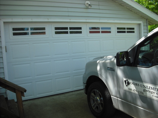 Picture of garage door with Doors Unlimited truck off to the side.